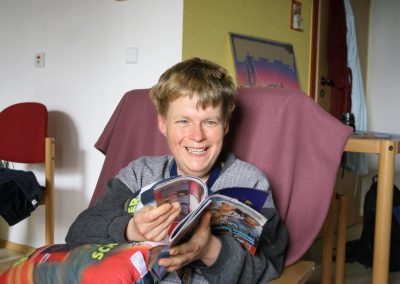 Ein Mann sitzt lachend auf einem Stuhl und liest eine Zeitschrift
