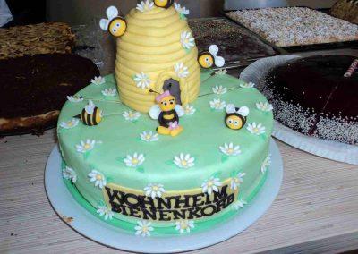 """Eine grüne Torte verziert mit Blumen, Bienen und einem Bienenstock, mit der Aufschrift: """"Wohnheim Bienenkorb"""""""