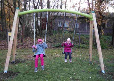 Zwei Kinder schaukeln auf einer grünen Wiese