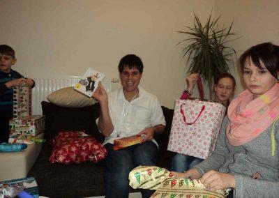 Ein junger Mann hält lachend eine DVD in der Hand. Neben ihm sitzt eine junge Frau mit einer Geschenktüte auf dem Schoß. Daneben sitzt ein Mädchen das gerade ein Geschenk ausprackt