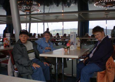 Drei Personen sitzen an einem Tisch
