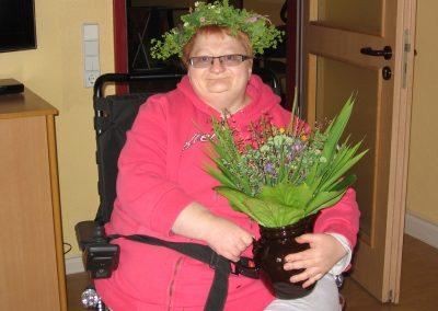 Eine Frau mit Brille sitzt in einem Rollstuhl und trägt einen Schmuck aus Blumen auf dem Kopf. Außerdem hält sie eine Vase mit Blumen in der Hand