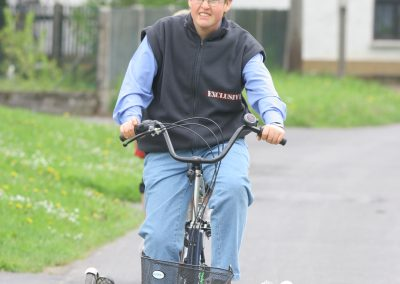 Eine Person mit Brille und schwarzer Weste fährt auf einem Fahrrad