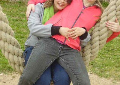 Zwei Mädchen sitzen auf einer Seilschaukel