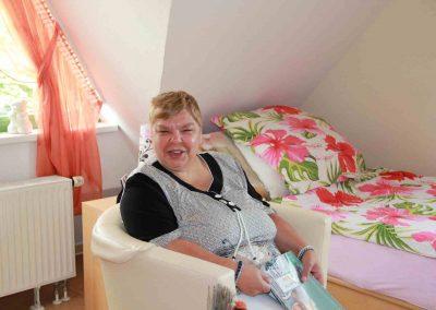 Eine Frau sitzt auf einem Hocker, neben ihr ist ein Bett mit geblümter Bettwäsche
