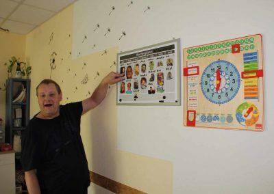 """Ein Mann zeigt auf einen Plan an der Wand, mit dem Text """"Wochenplan"""""""