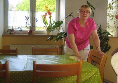 Eine Frau wischt mit einem Lappen einen Tisch ab.