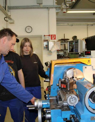 Ein Mann in einem Blaumann erklärt zwei Personen eine Maschine