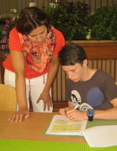 Ein junger Mann mit Armbanduhr füllt unter Aufsicht einer Frau mit Halstuch einen Fragebogen aus