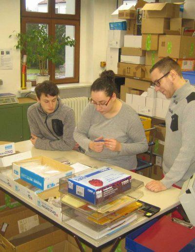 Eine Frau steht mit zwei jungen Männern an einem Schreibtisch und füllt einen Zettel aus, in einem Regel stehen viele Kartons und Schreibwaren
