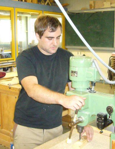 Ein Mann arbeitet an einer Maschine mit einem Stück Holz