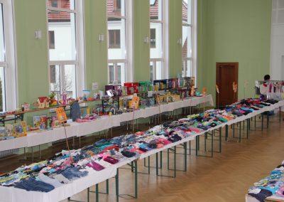 Kinderspielzeug und Kleidung auf mehreren großen Tischen.