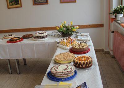 Mehrere Kuchen und Torten auf einem Tisch mit Tellern und Tassen.