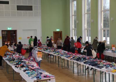 Mehrere Tische sind nebeneinander aufgestellt und bilden eine lange Reihe. Auf den Tischen liegen Kleidungstücke für Kinder in verschiedenen Größen. An den Tischen gehen Personen vorbei und betrachten die Kleidung.