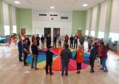 Mehrere Personen stehen im Kreis um ein großes Stofftuch, das viele verschiedene Farben besitzt.