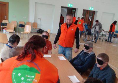 Mehrere Personen sitzen mit Augenbinde an einem Tisch. Vor ihnen liegt eine leere Pappschale auf dem Tisch. Zwei Personen in orangenen Westen beobachten sie.