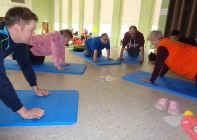 Mehrere Personen knien auf blauen Gymnastikmatten.