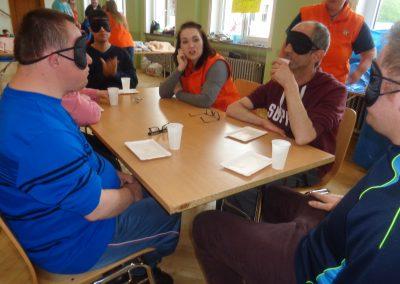 Mehrere Personen sitzen mit Augenbinde an einem Tisch. Vor ihnen liegt eine leere Pappschale und ein Plastikbecher auf dem Tisch. Zwei Personen in orangenen Westen beobachten sie.